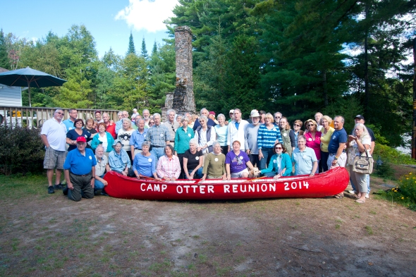 Otter alumni and families gathered Saturday afternoon at the lakeshore site of Camp Otter.  The chimney from the Camp's main lodge rises behind them.  The canoe was prepared especially for the event by Otter cottager and former head of the Lake Cottagers Association, Larry Cassie.